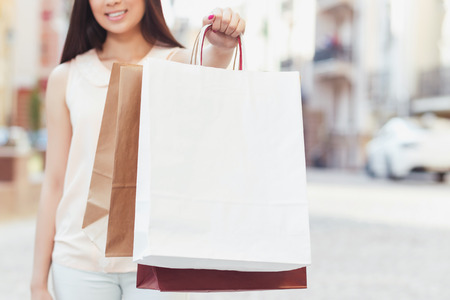 gift bags: Portrait of a young girl wearing beige blouse and white jeans stretching her hand holding shopping bags in front of her, selective focus, beautiful old city on the background