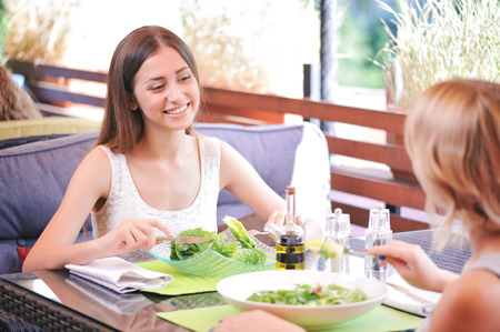 salad fork: Smiling brunette sitting in cafe with her lovely girlfriend and eating salads.