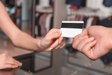 trade credit: Young happy woman stretching out a credit card to the salesman in a store Stock Photo