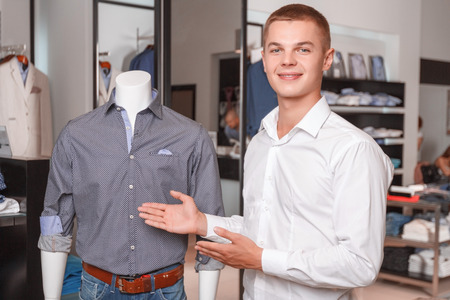 sales assistant: Young attractive sales assistant demonstrating clothes in his shop