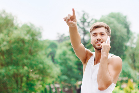nice guy: Vivacious nice guy holding mobile phone and talking on it while pointing up. Stock Photo