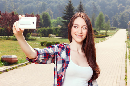 laugher: Close up of smiling young girl holding mobile phone and making selfie Stock Photo