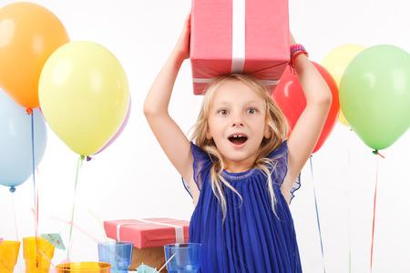 그녀의 머리에 선물을 들고 즐거운 어린 소녀