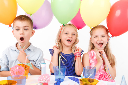 birthday party kids: Cheerful children holding balloons and sitting at the table. Stock Photo