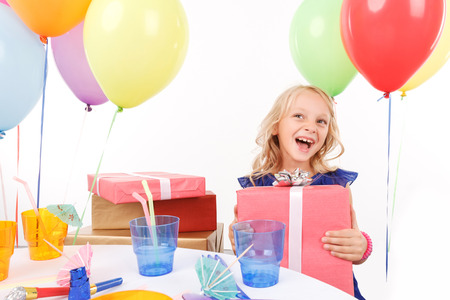birthday presents: Smiling upbeat girl sitting at the table and holding bright