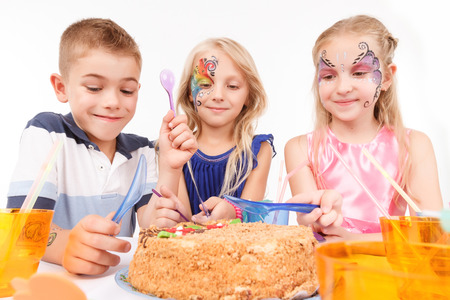 nice: Nice little children sitting at the table and waiting to taste festive cake. Stock Photo