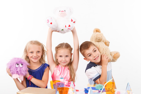 upbeat: Upbeat positive children holding hands up in the air while playing with soft toys.