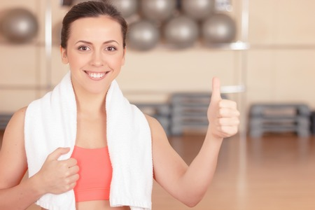 youthful: Thumbs up. Portrait of youthful pleasant woman standing in gym wit towel on her shoulders and thumbing up. Stock Photo