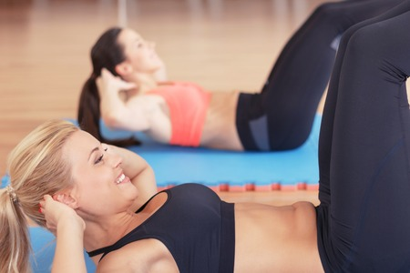 close p: Working hard. Close p of pair pretty strong sportswomen doing abdominal crunches in gym together.