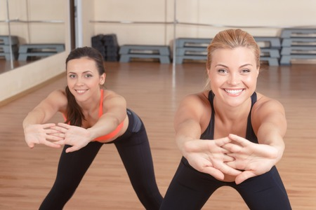 leaning forward: Always forward. Portrait of pair pretty strong sportswomen doing stretching exercises by leaning forward. Stock Photo