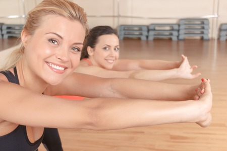 lean out: Leaning to purpose. Pretty blond-haired woman with her friend doing stretching exercises by leaning forward.