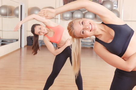 lean out: With great enthusiasm. Pair of strong and sportive women doing stretching exercises in gym. Stock Photo