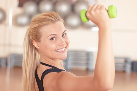 keeping fit: Keeping fit. Beautiful smiling woman doing fitness exercises by using little dumbbells in gym