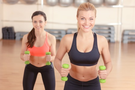 persistent: Holding hard. Two persistent women doing weights fitness exercises by using little dumbbells in gym