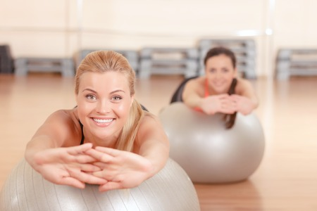 lean out: Forward to you. Pretty blond-haired woman with her friend doing stretching exercises on fitness ball in gym.
