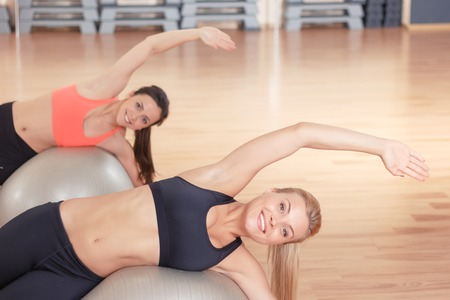 lean out: Stretch with smile. Pair of sportive women lying on fitness balls and doing stretching exercises in gym.