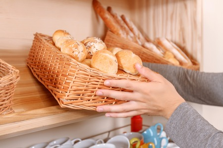 close out: In process. Close up portrait of young man setting out goods on stalls in bakery. Stock Photo