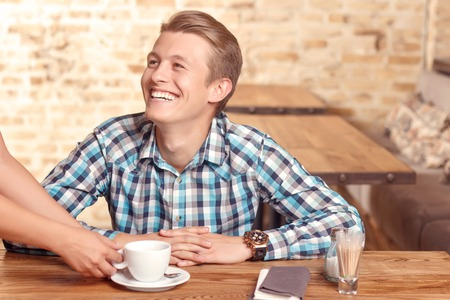 sincerely: Nice service. Young sincerely smiling man is being sereved by waitress in cafe