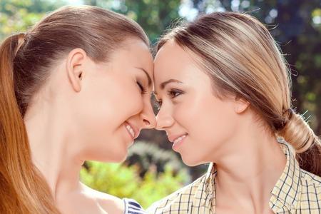 Amor lesbiano. Close up retrato de dos mujeres bastante lesbianas jovenes que ligan en el parque.