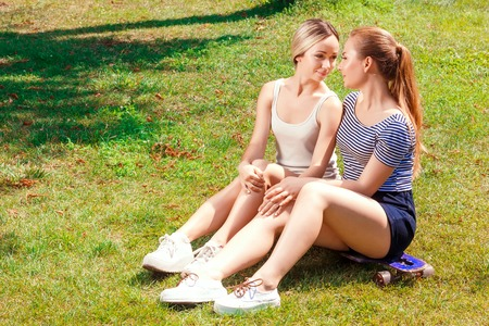 lesbian: Comfort of solitude. Portrait of two young attractive lesbian women sitting on skate board in park and flirting. Stock Photo
