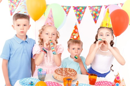 Party horn. Little cute kids sitting at adorned table with birthday cake on it and blowing party horn. Stock Photo