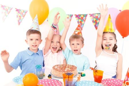 Emotionen zum Ausdruck bringen. Gruppe glückliche lächelnde kleine Kinder ihre Arme nach oben während große Geburtstagsparty zu erhöhen.