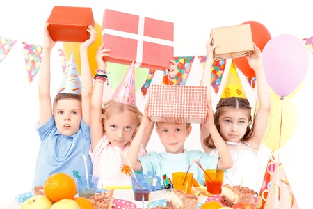 birthday present: Higher to sky. Little happy children lifting birthday presents during party.