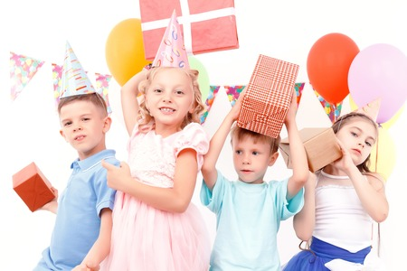 kids birthday party: So fancy. Little cheerful kids posing with colorful birthday presents during party.