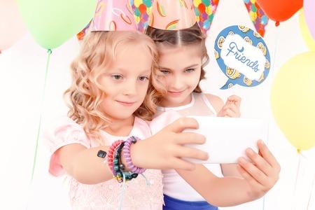 birthday hat: Friends forever. Two pretty joyful girls doing selfie during birthday party.