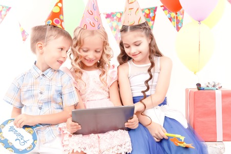 kids birthday party: Different emotions. Group of little cheerful kids sitting at table during birthday party.