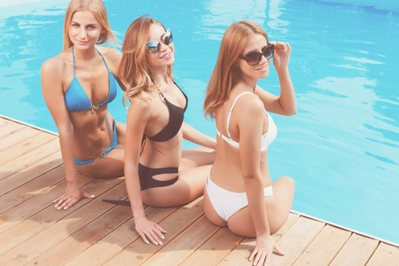 chilling out: Chilling out. Portrait of three young pretty ladies in bikini sitting at poolside during summer vacation.
