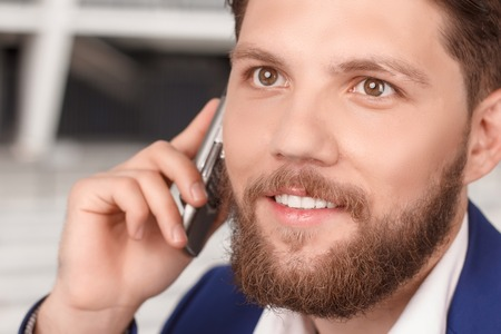 busy beard: Being busy. Close up portrait o young handsome man with beard talking per mobile phone. Stock Photo