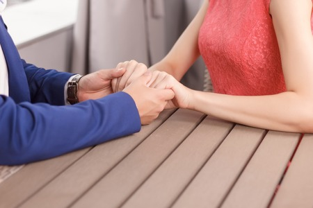 feel affection: Strong love. Close up portrait of young couple holding hands of each other. Stock Photo