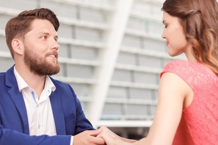 hold hands: Real emotions. Portrait of young handsome man looking at his lovely girlfriend and holding her hands Stock Photo