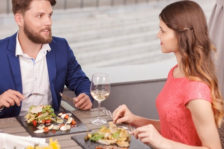 intent: Intent glance. Beautiful couple having meal and looking at each other in restaurant. Stock Photo