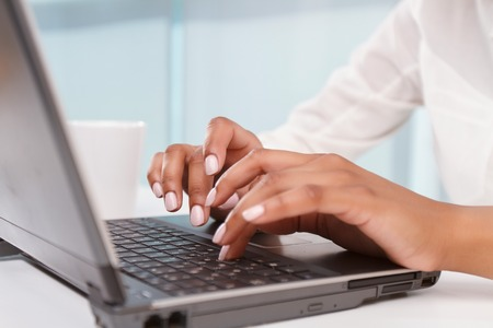 mulatto woman: Fast fingers. Close up portrait of young mulatto woman typing on laptop.