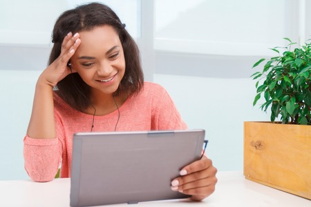 mulatto woman: Funny videos. Smiling young mulatto woman sitting, excitedly using tablet and touching her head with her hand. Stock Photo