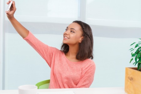 mulatto woman: Office selfie. Young and smiling mulatto girl sitting at desk in office and doing selfie. Stock Photo