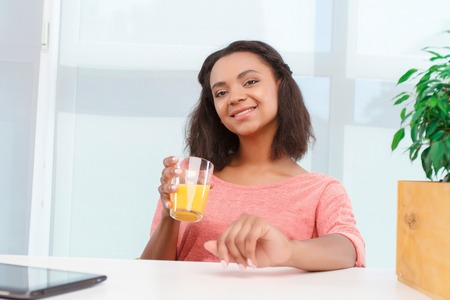 mulatto woman: Freshly made. Pretty young mulatto girl sitting at desk in office with glass of orange juice. Stock Photo