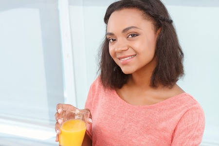 half dressed: Healthy diet. Young attractive mulatto holding with glass of orange juice on background of big window. Stock Photo