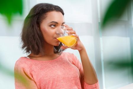 mulatto woman: Full of vitamins. Young attractive mulatto woman drinking orange juice on background of big window.