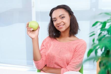 youthful: Lunch time. Portrait of youthful beautiful mulatto girl holding fresh green apple on background of big window.