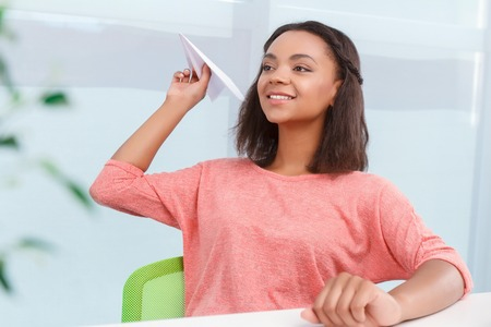 confident woman: Lets be childish. Pretty young and smiling mulatto woman sitting at desk in office and throwing paper plain to her colleague. Stock Photo