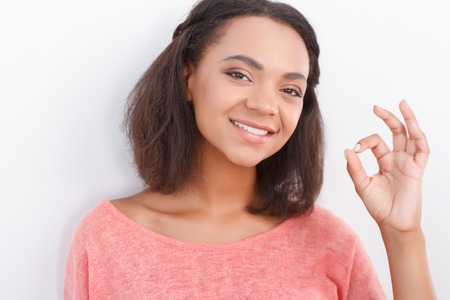 mulatto woman: Everything is ok. Pretty nice mulatto woman showing ok with her fingers on white background Stock Photo