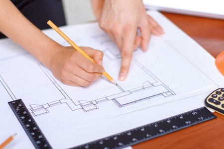 Lets do our work. Professional diligent architect holding pencil and drawing plan while being busy at work