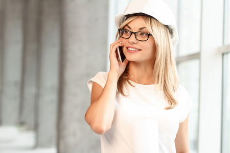 to be pleasant: Time to be successful. Pleasant cheerful attractive female architect talking on mobile phone and evincing happiness while working. Stock Photo
