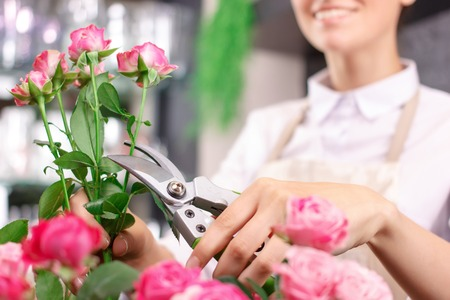 upbeat: Dedicated to job. Nice upbeat  charming female florist holding garden scissors and smiling while being involved in work