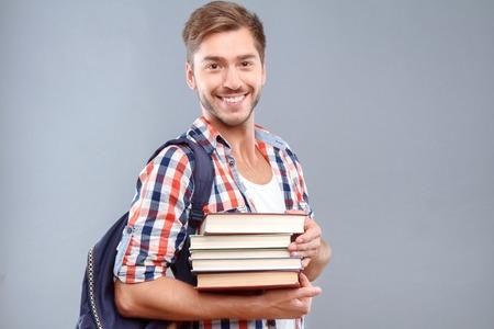 Boldog diákok életét. Szép vidám fiatal diák gazdaság könyvek és kifejező öröm állva elszigetelt szürke háttér.