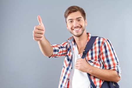 Life is great. Cheerful nice young student holding hand up and thumbing up while evincing gladness. Reklamní fotografie