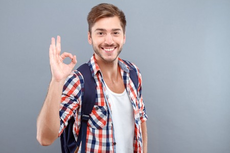 elated: Everything is great. Elated upbeat young student holding hand raised and showing ok while reveling in joy Stock Photo